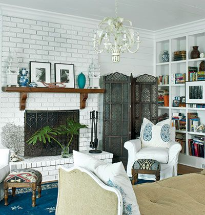 Coastal living room on Cat Island in South Carolina with a white-painted brick fireplace, shelf mantel