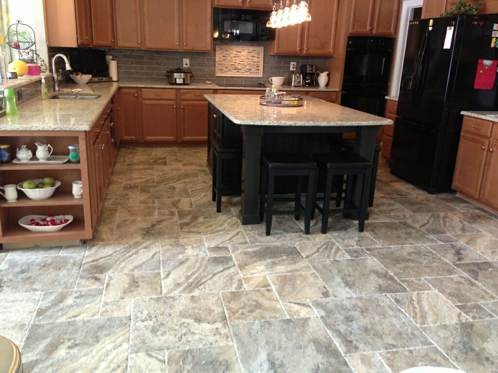 This porcelain tile floor has a rustic travertine look in a modular