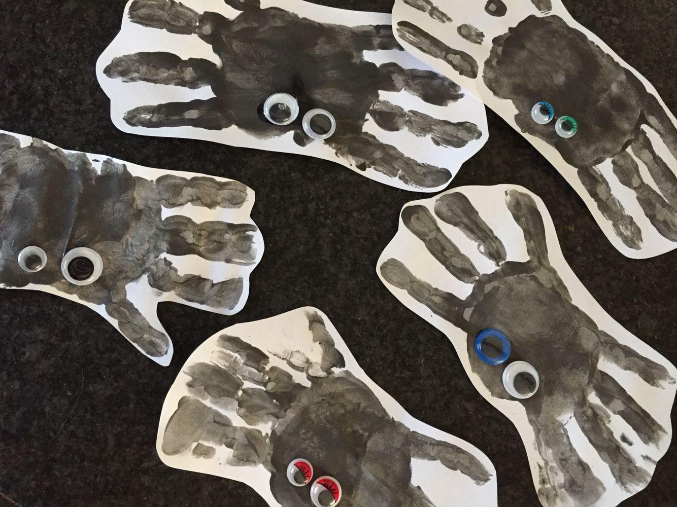 Spinnen van zwart geverfde handen met wiebeloogjes.