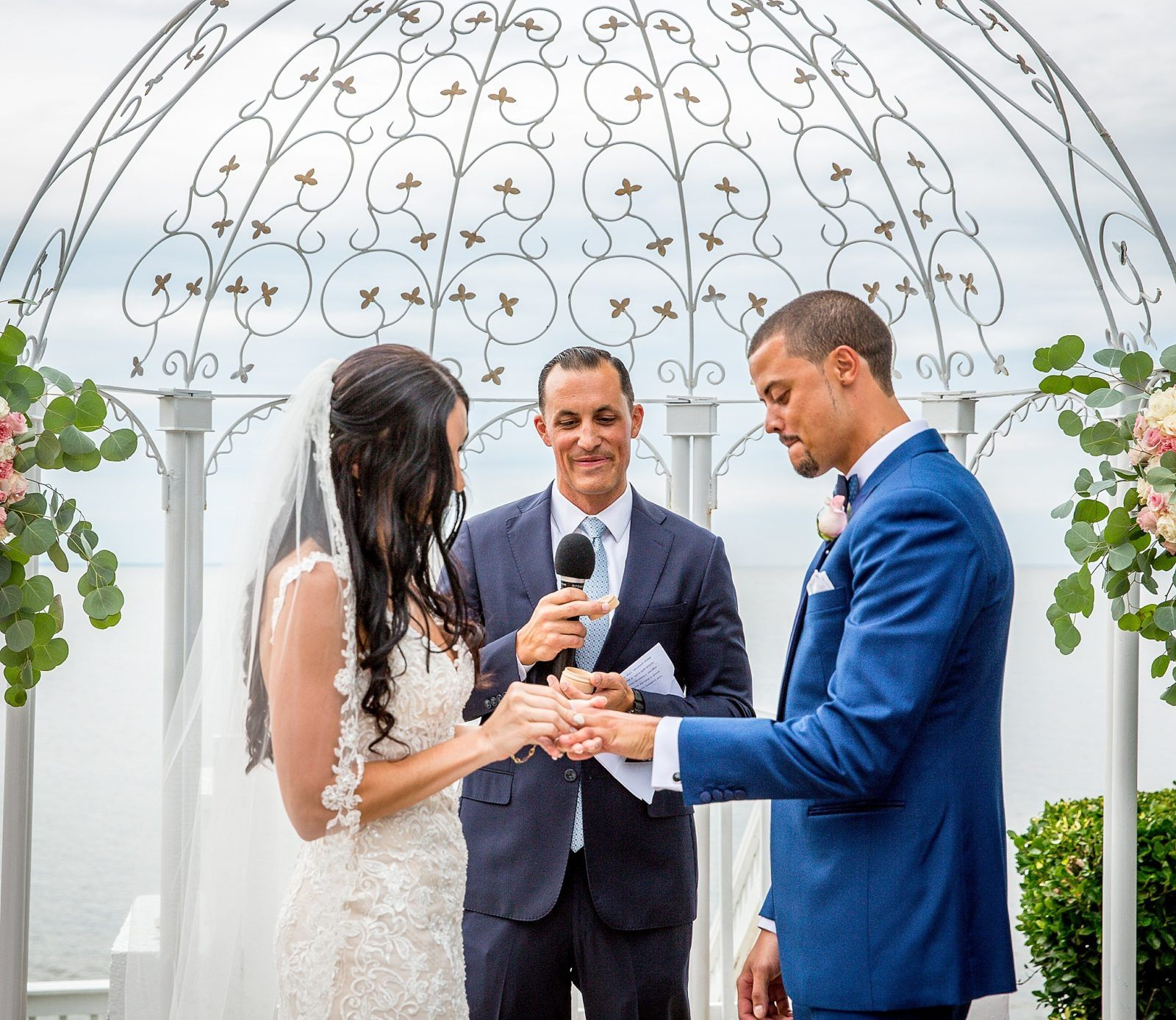 Bride and groom exchanging vows during waterfront ceremony