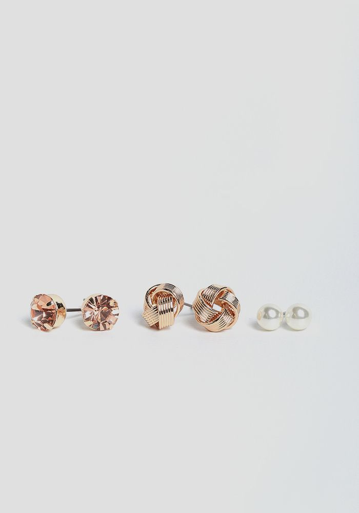 24397fae3 This elegant set of earrings feature a gold-toned knot, a faceted peach gem,  and a faux pearl stud. Pair these stunning earrings with your favorite  dresses ...