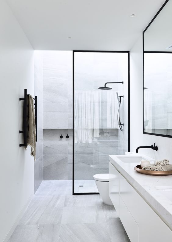 a modern space with grey marble tiles, white cabinets, black frame ...