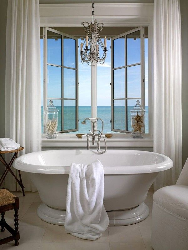 Vintage freestanding bathtub next to the window with sea view in a ...
