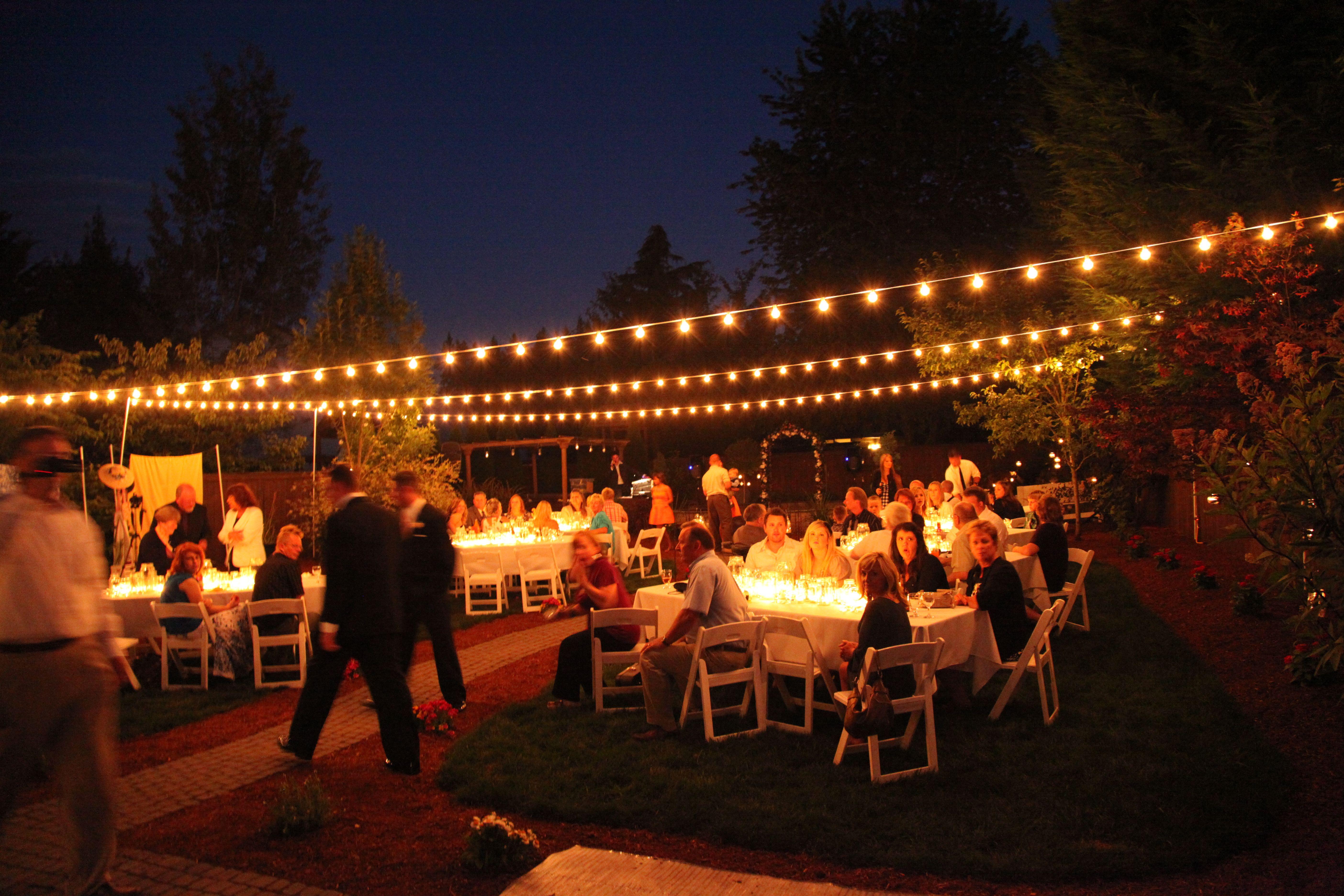 Backyard wedding with italian string lights hung overhead ...