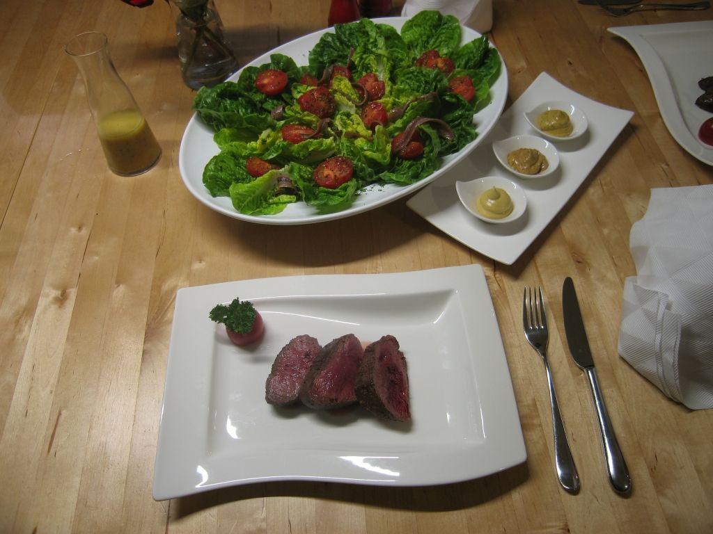 Wir haben ein neues Kochbuch. Darin wird ein Salat mit Sardellen, Salatherzen und Tomaten vorgestellt. Wir haben es mit Steak verfeinert.