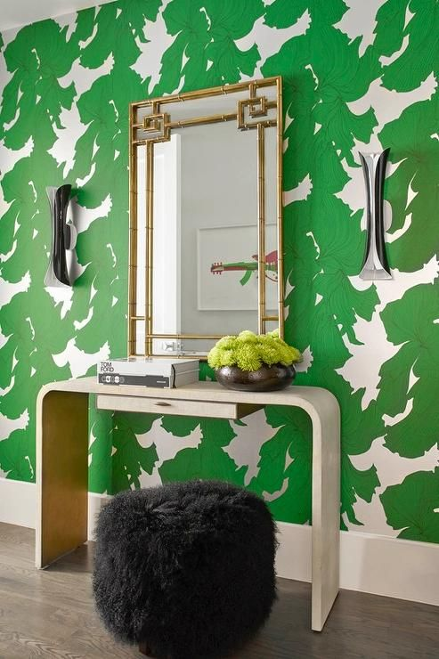 Green and gold contemporary foyer boasts walls clad in green leaf pattern wallpaper illuminated by modern black sconces mounted on either side of a gold bamboo mirror fixed above a gray waterfall console table paired with a black sheepskin pouf.