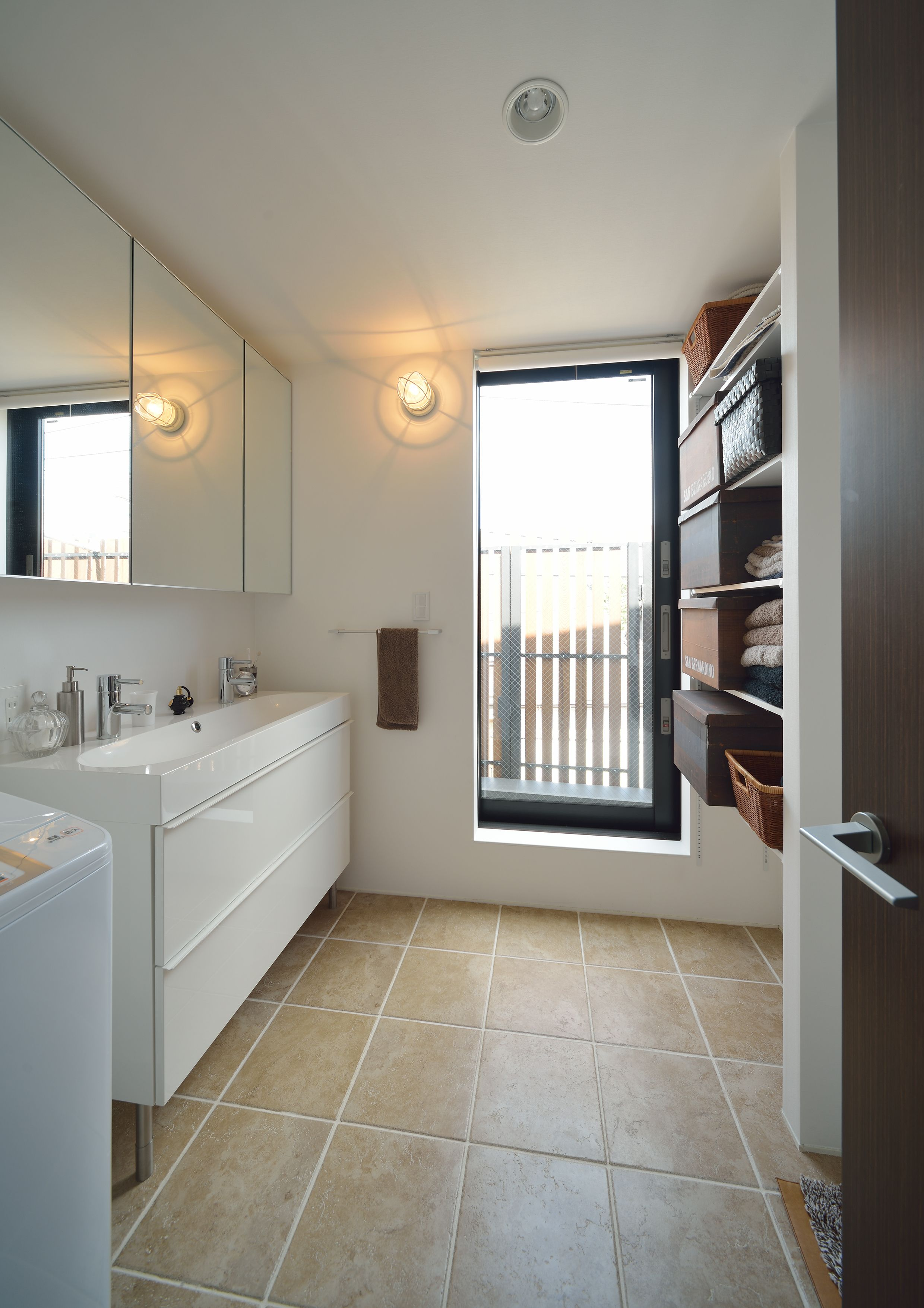 ベランダからの明るい光と床タイルが斬新な洗面所 洗面所 タイル