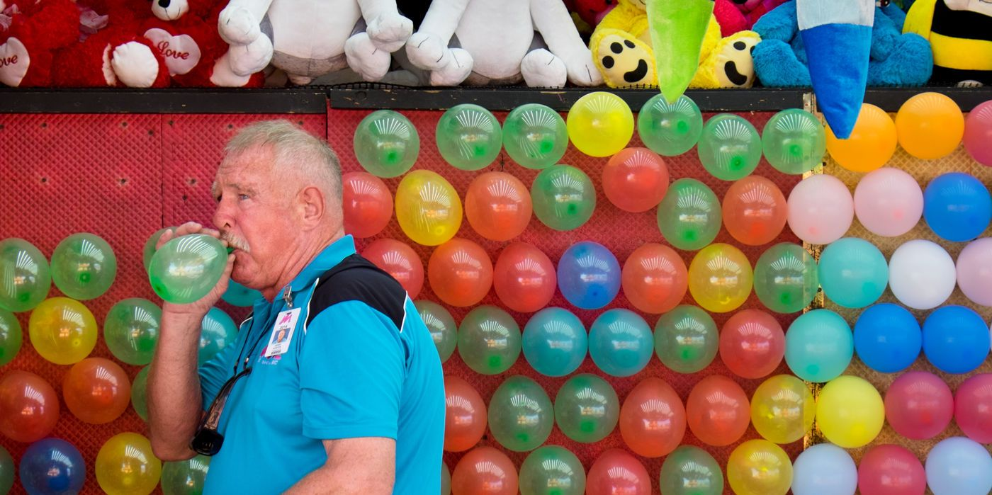 2014 Nebraska State Fair: Hank Norton with Wade Shows blows up balloons for his Prize Time game booth on the opening day of the Nebraska State Fair in Grand Island on Friday, August 22, 2014. By: KENT SIEVERS/THE WORLD-HERALD