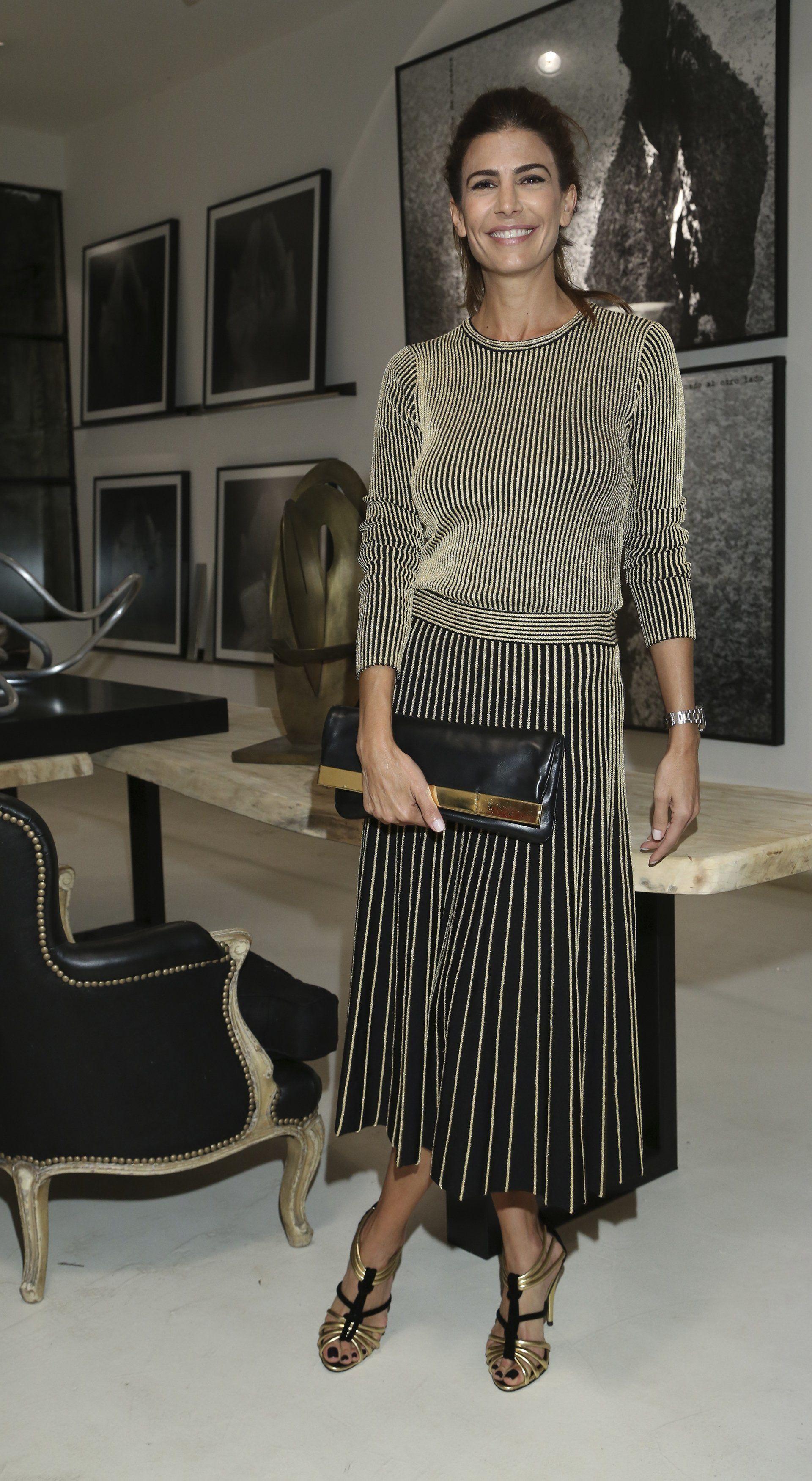 Como en cada una de sus apariciones públicas, Juliana Awada impactó con su look. Para la ocasión, eligió un vestido negro con rayas doradas de escote redondo y mangas largas. Lo acompanó con sandalias y un gran sobre de cuero haciendo juego