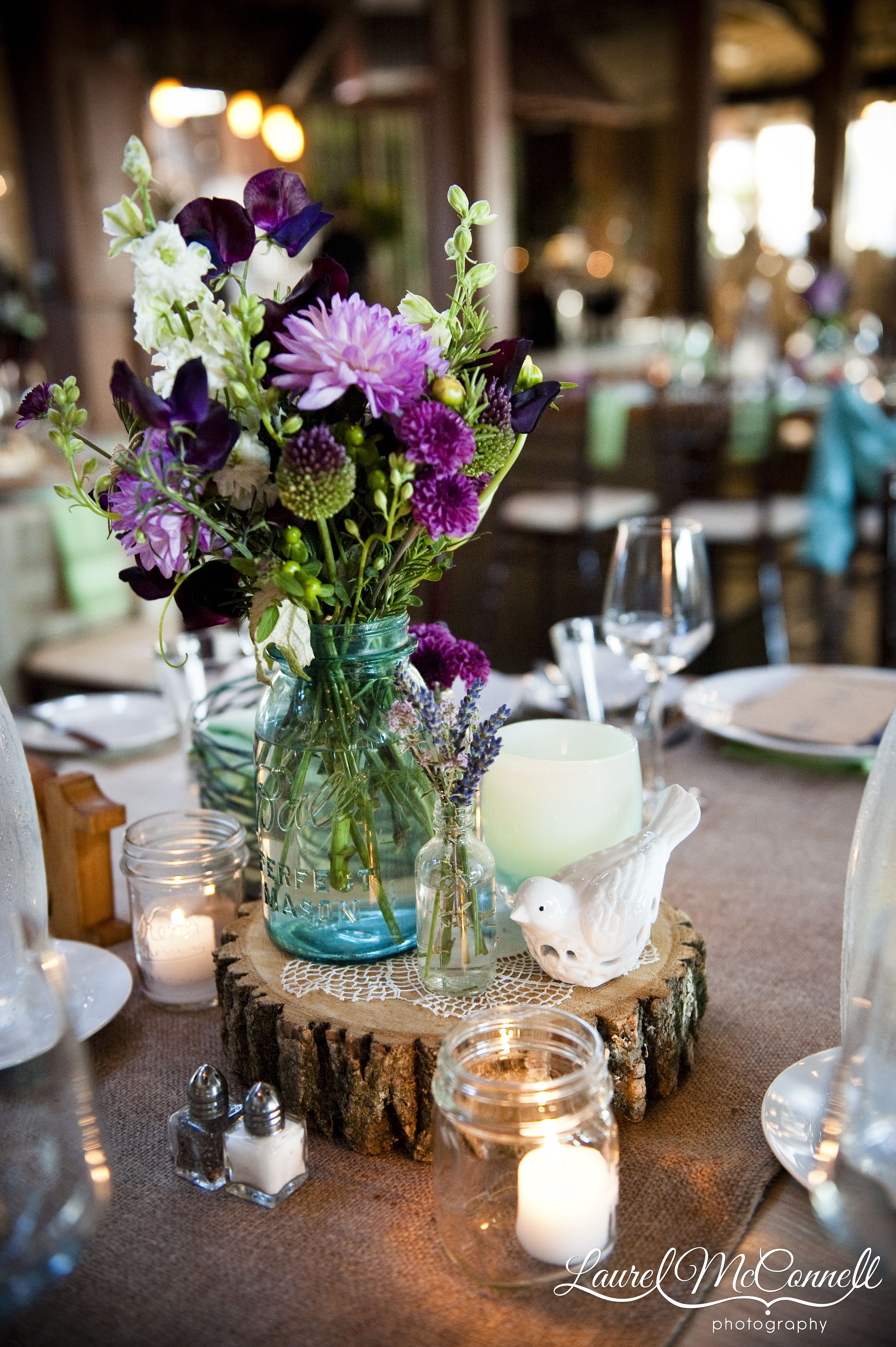 Wood Rounds Centerpieces - The final centerpiece was a wood slice with a vintage blue ball jar of flowers