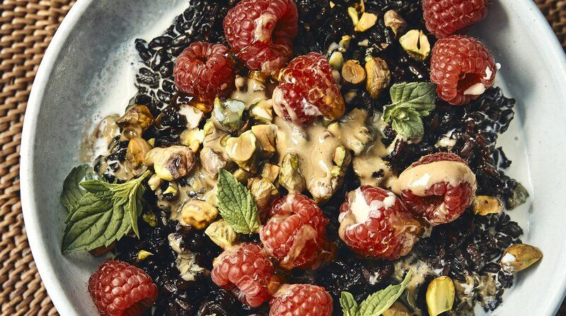 Black rice bowl with tahini pistachios and raspberries
