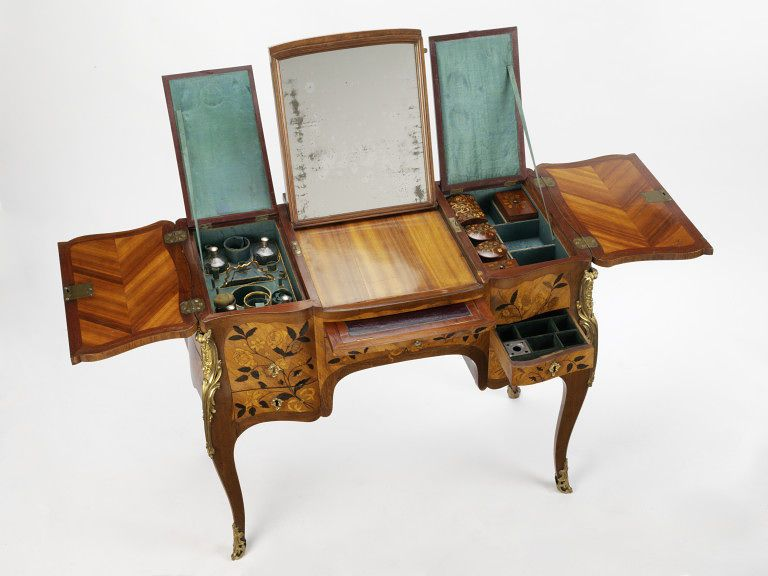 Dressing table, France, 1760-1770, Oak; Sycamore; Tulipwood; Purplewood; 4 drawers velvet lined fitted with 3 silver containers for writing materials. Leather covered pull-out writing desk. Top divided into 3 sections-central one hinged adjustable mirror. Side sections fold out. Left—compartment silk lined fitted with toilet articles: 4 glass bottles with silver screw tops, 1 glass, a gilt tray & a brush. Right fitted with 2 cylindrical, 2 rectangular wooden toiletboxes & clothesbrush.