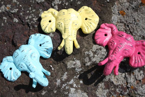 A Trio of Elephant Heads/Wall Hook/Coat Hook/Cast Iron in Berry Pink, Sea Blue and Yellow. $35.00, via Etsy.