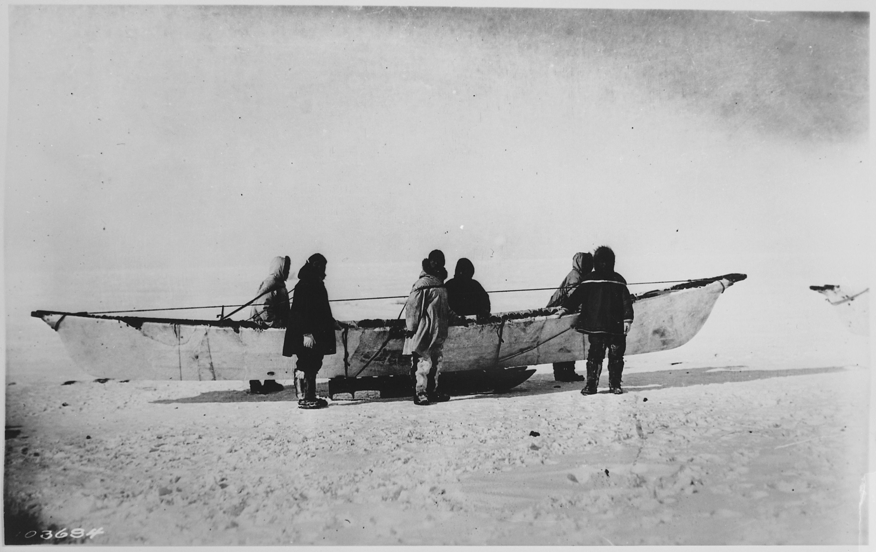 Six_Eskimos_standing_beside_native_skinboat_(umiak)_on_sled,_Point_Barrow,_Alaska,_1935