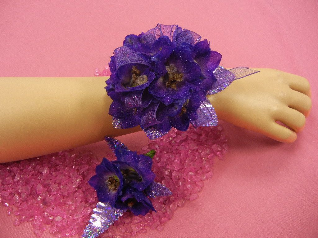 Flowers By Frances: Dark purple delphinium, purple sparkle ribbon, and purple laser leaves. Corsage and matching boutonniere designed using customers ideas.