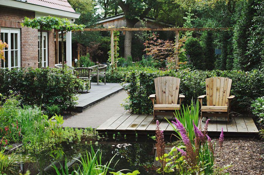 Modern klassieke tuin vlonder met luie stoelen aan de vijver