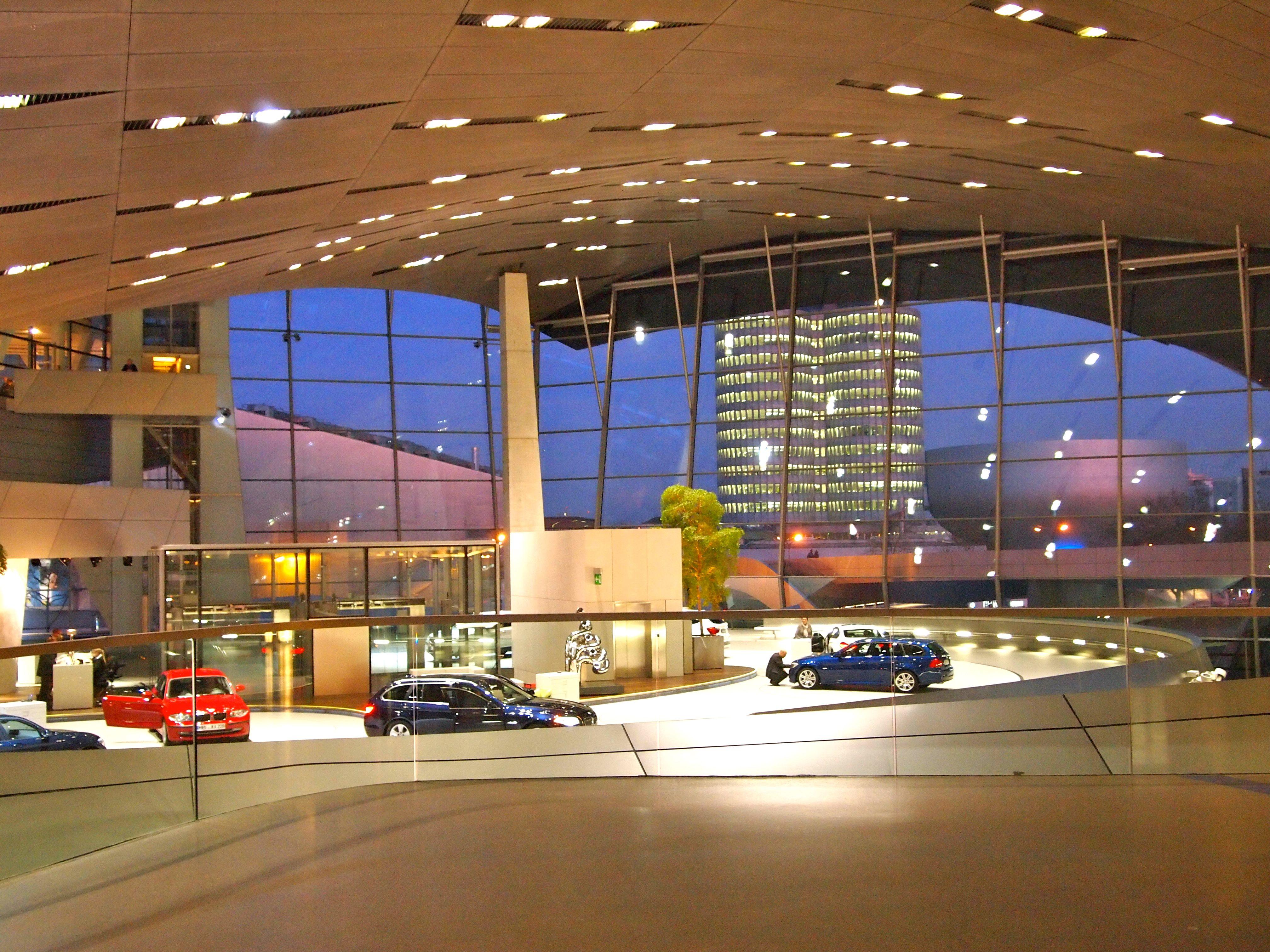 """BMW-Welt in München. Große Austellungsfläche mit aktuellen und historischen BMW-Fahrzeugen. Im Hintergrund der """"Vierzylinder"""", das Verwaltungsgebäude von BMW."""