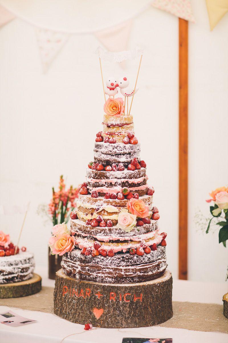 Naked cake em que as frutas e flores fazem a cor do bolo e o powder sugar e o creme de recheio faz a cor branca.