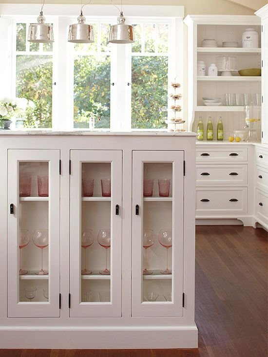 A banquette-island combo installed in this kitchen makes the most of the room's limited real estate. In addition to providing plenty of prep space, the banquette creates separation between the kitchen and formal dining room. Glass-panel cabinet doors on the dining room side of the unit provide storage space for pretty drinking glasses.