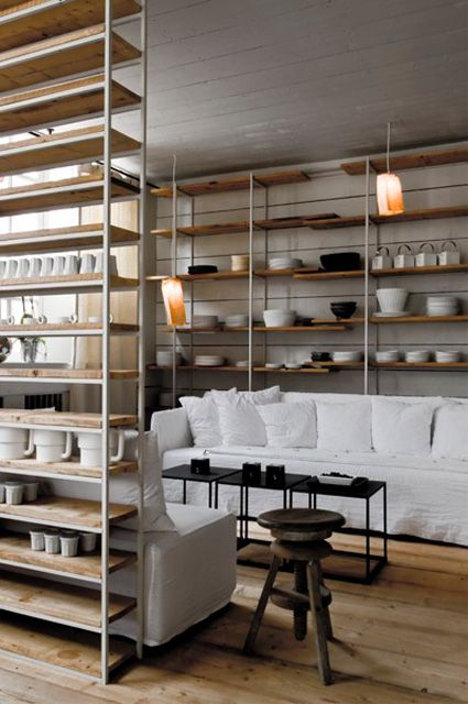 open shelves stacked with white china and comfortable seating