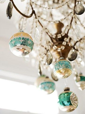 I hang mercury glass ornaments in the same colors from my dining room chandelier, with an aqua rafia.  The light reflecting off of them looks soo pretty!