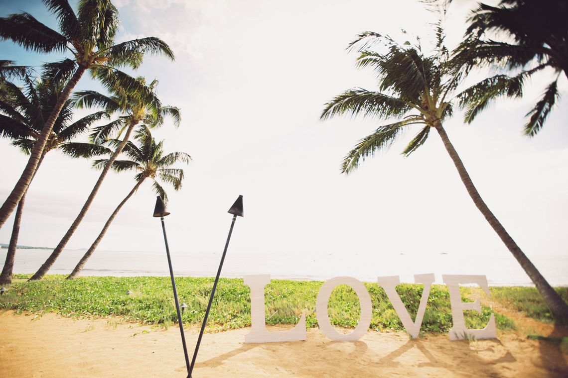LOVE sign with palm trees and Pacific Ocean in the background, set up on the side of the wedding ceremony as a great prop for the couple and guests to pose and take photos. | photo: Anna Kim Photography