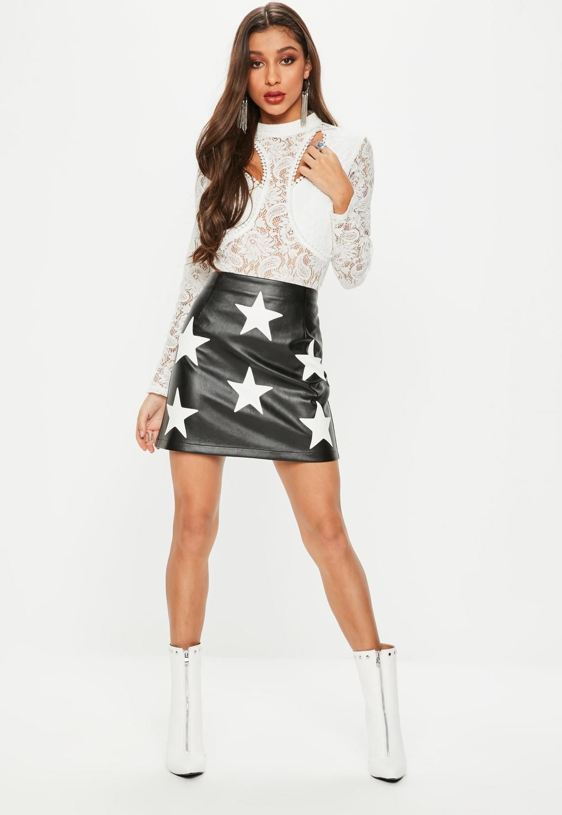 78e8cb1d1e37 This faux leather mini skirt features in a black hue, with white star  print, a line design and concealed zip fastening.