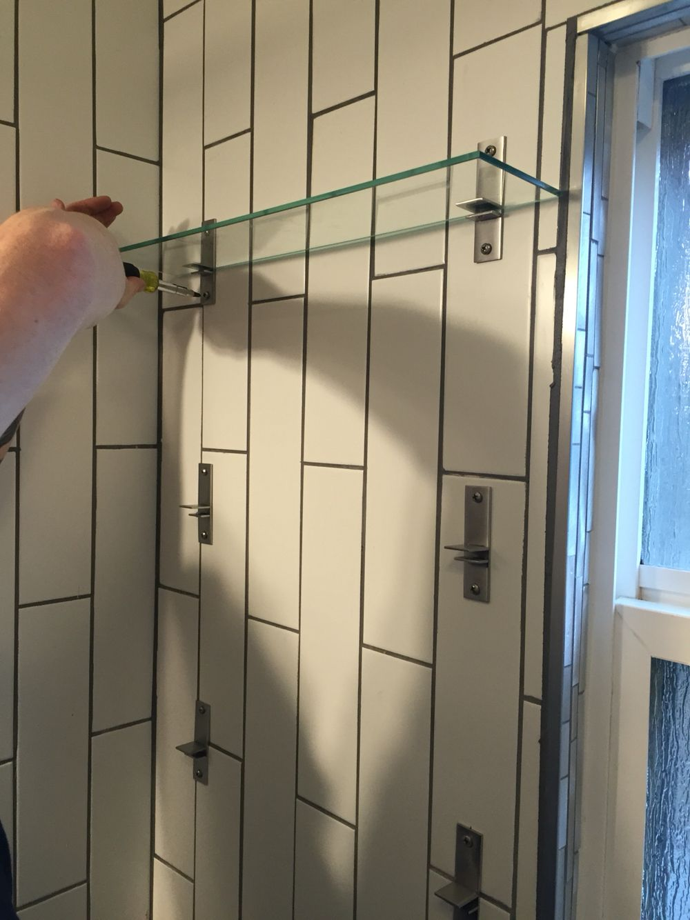 Glass shelves in the shower instead of a spring loaded