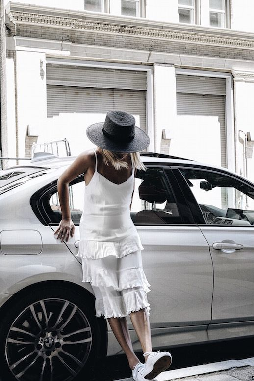White dresses. Pleats. Breezy, chiffon fabrics: The epitome of heated summer weekends. This fashion blogger achieved a pretty and laidback look in a white pleated midi dress, white sneakers and an off-black straw hat. It's a look we can all appreciate and admire.