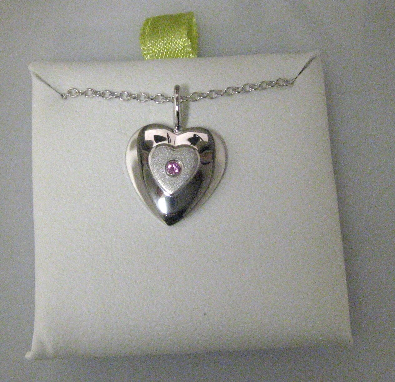 Sterling silver infant heart pendant with a  pink sapphire in the center.