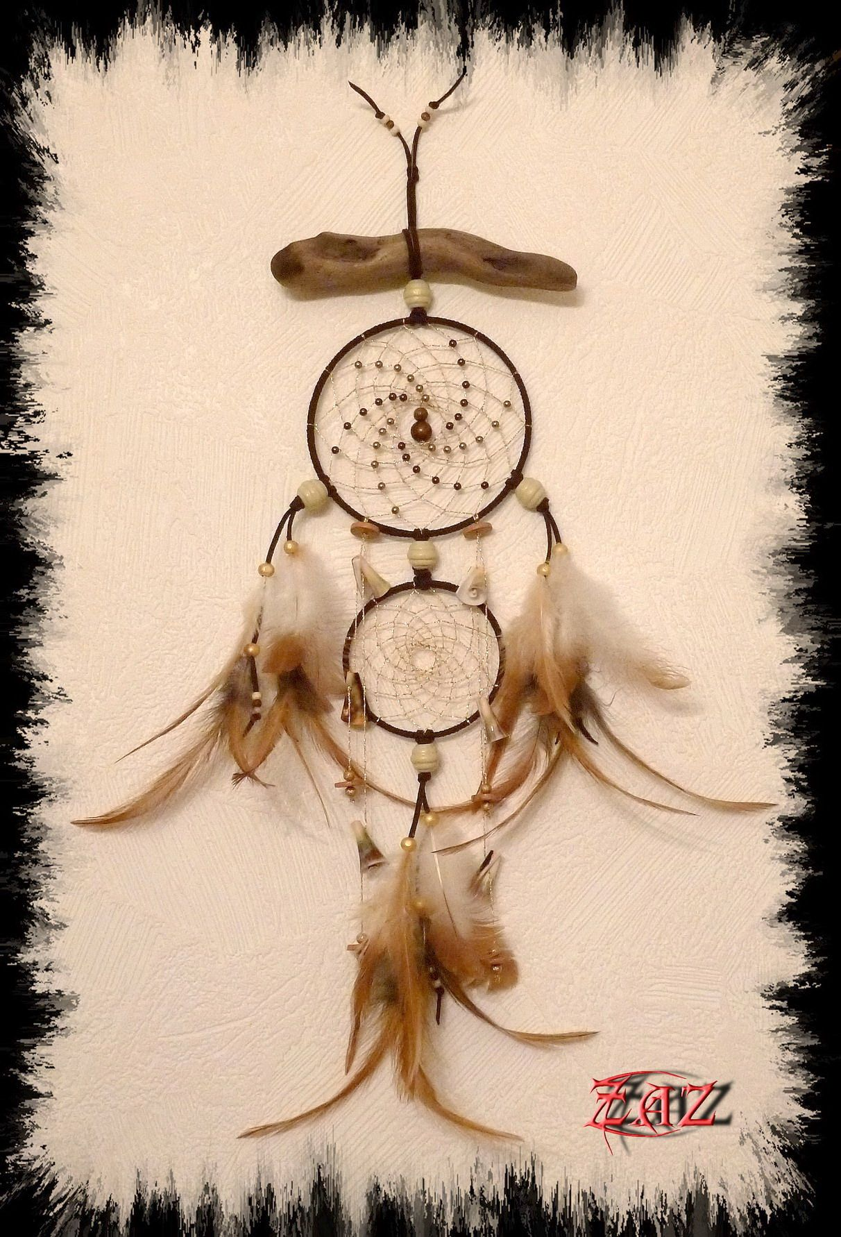 Dreamcatcher with glass, wood and shell beads on a piece of driftwood