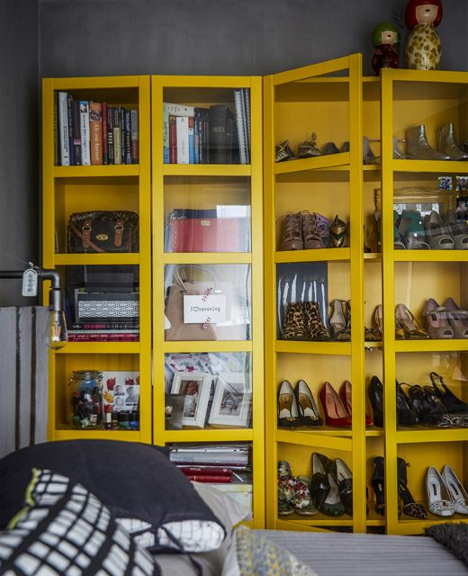 A Yellow Cabinet Displaying Shoes And Books.