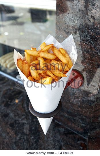 Potatoes fries in a little white paper bag hanging at the wall from a belgian friterie - Stock Image
