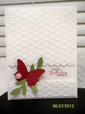 Red butterfly on white embossed card.