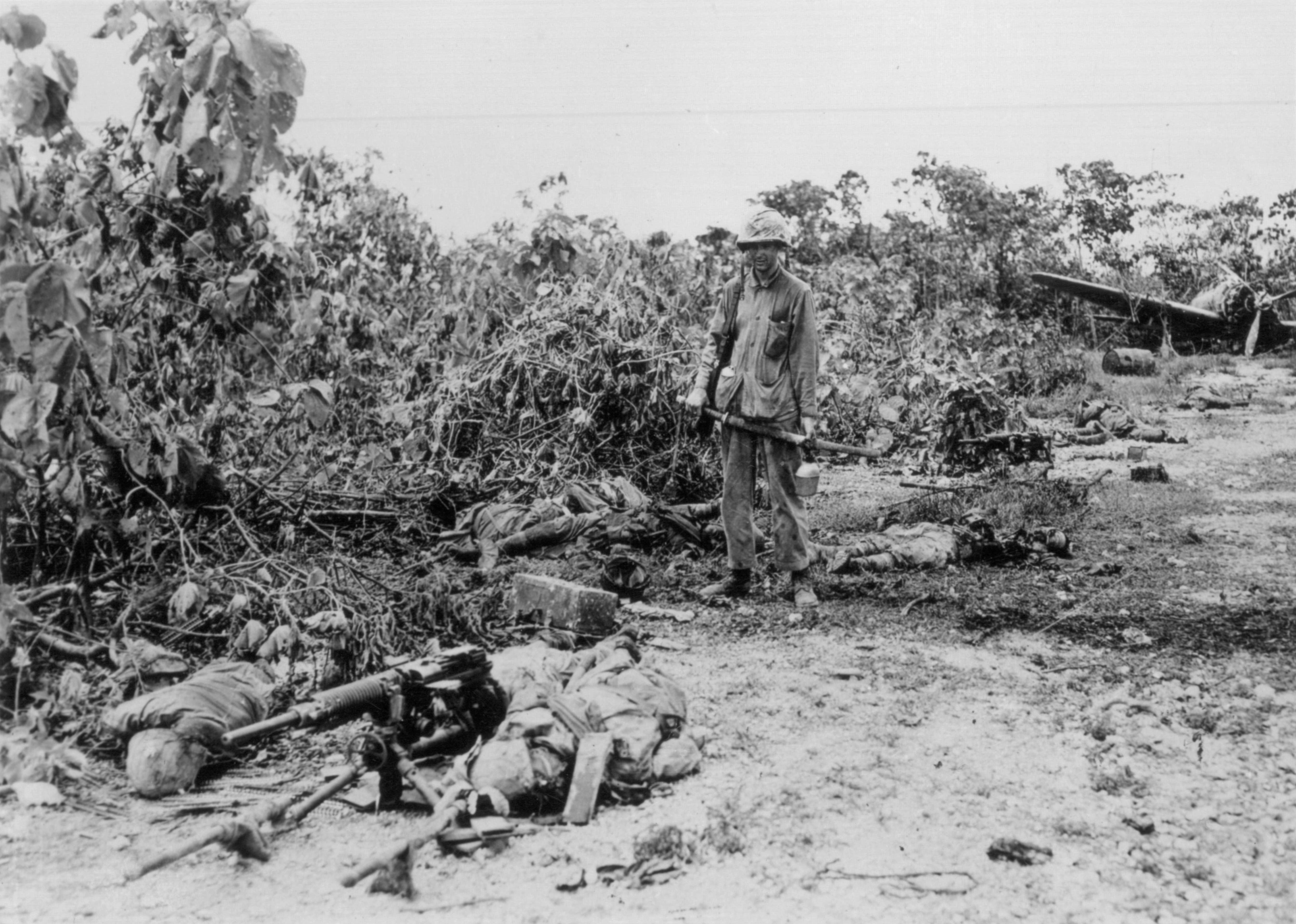 US Marine stands amid several dead Japanese soldiers. He ...