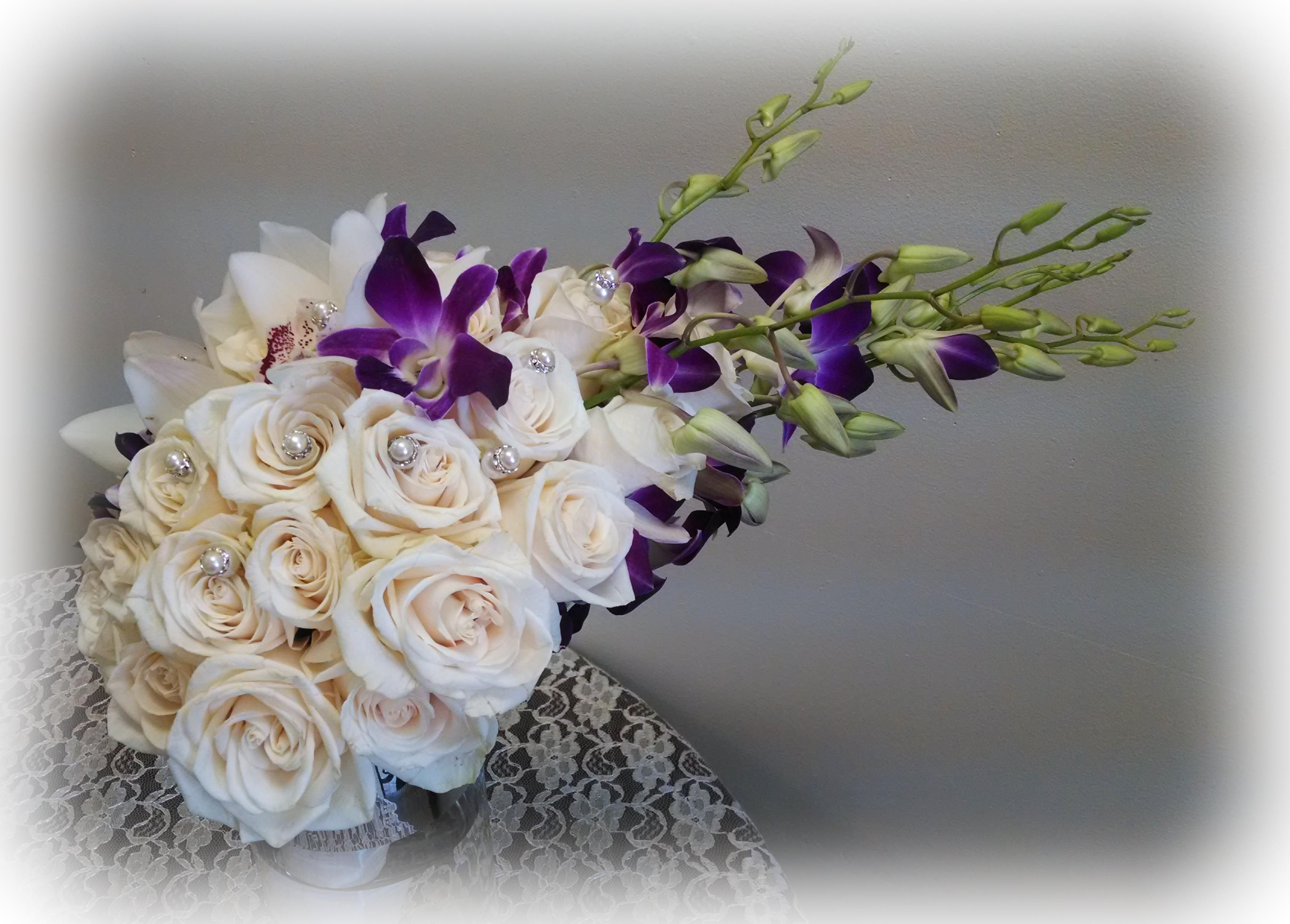 White roses and purple orchids in a spread design with perls