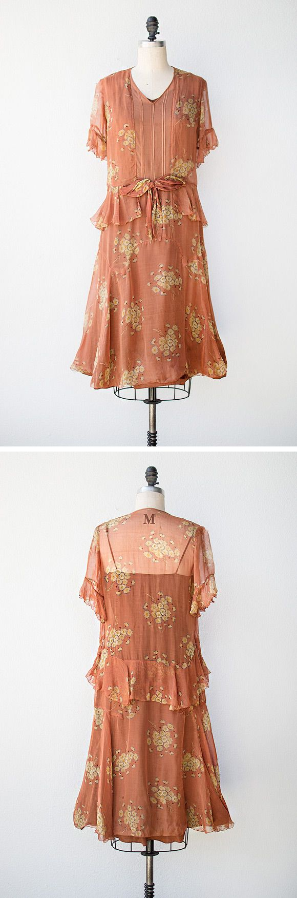 1920s dress made of gauze and is lined with a fabric that feels like silk. The copper colored fabric has a cute floral print. The bodice has a v-neckline, flutter sleeves, and pleating down the center front. A peplum ruffle and bow accentuate the drop waist.