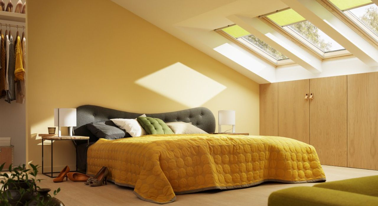 In this bedroom with high knee walls, three manually operated VELUX ...