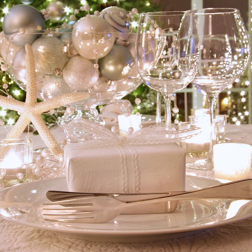Elegantly Lit Holiday Dinner Table With Wine Glasses And White Ribboned Christmas Table Centerpieces Decorating With Christmas Lights Christmas Table Settings