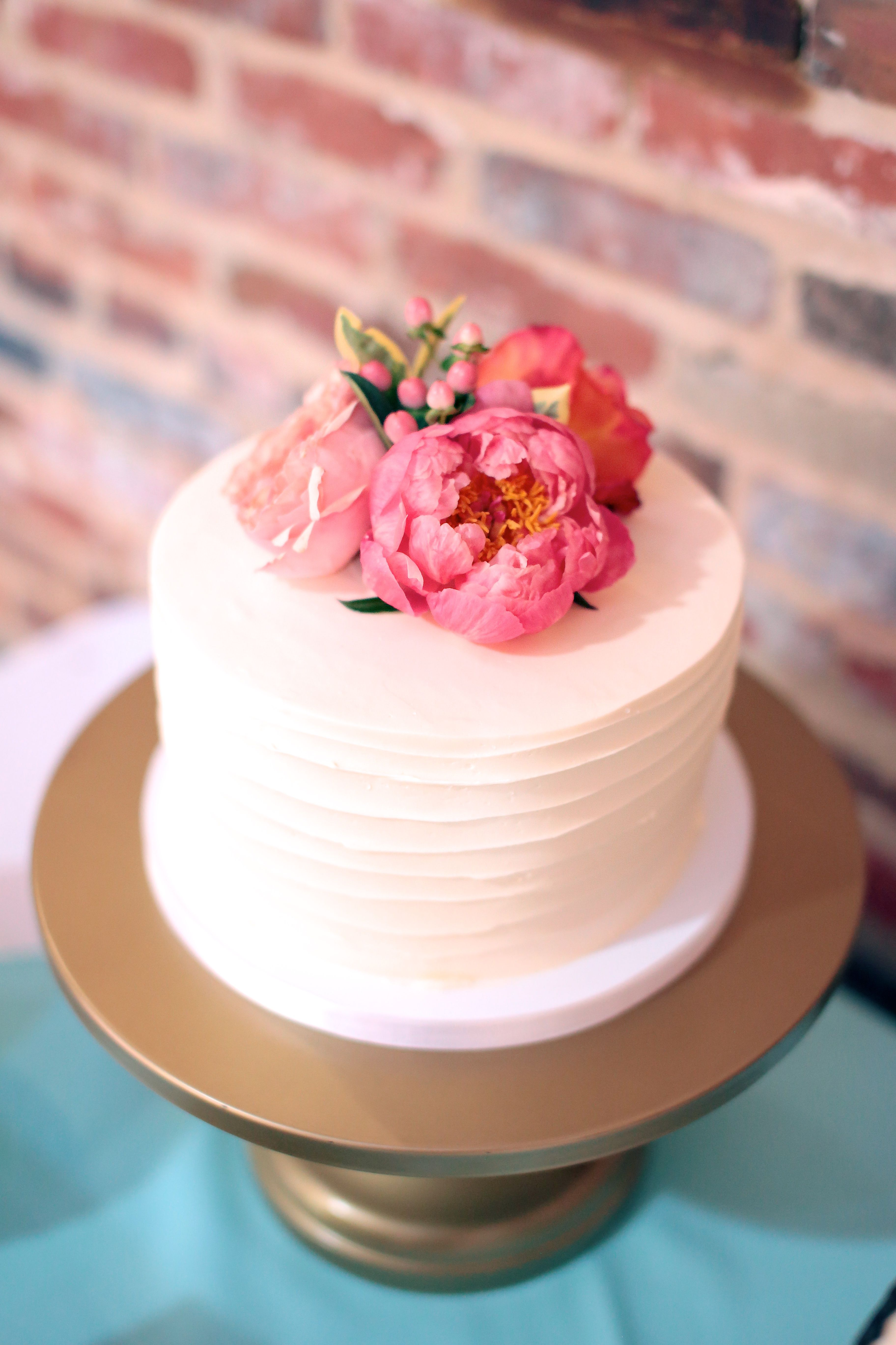 Small textured buttercream wedding cake with fresh flowers. Photo by ...