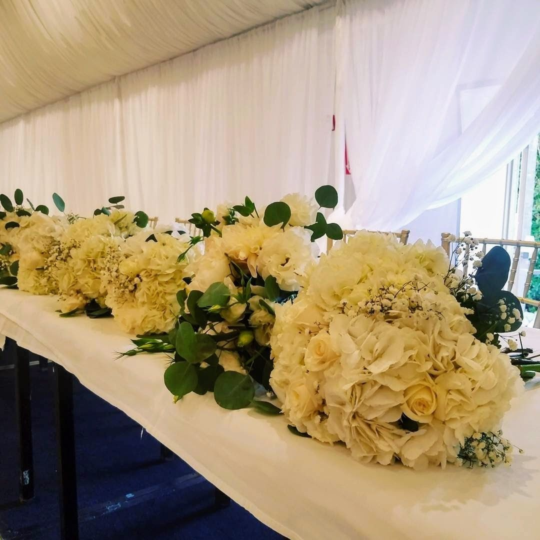Winter white wedding reception low centerpieces by Buen Gusto ... on