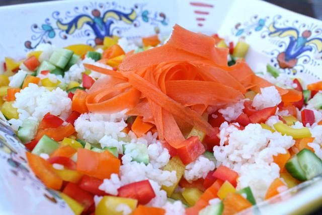 A recipe for sushi rice salad made with sushi rice, bell peppers, carrots, and cucumber, drizzled with a wasabi vinaigrette.