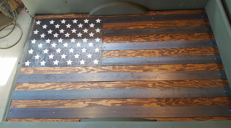 Metal American flag sitting on top of the wood bed floor