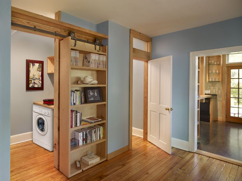 Sliding Bookcase On Salvaged Barn Track To Conceal Laundry