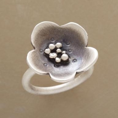 "FLOATING FLOWER RING -- Like a windblown blossom afloat on a lake, a winsome flower rests upon our exclusive ring. Handcrafted in USA of recycled sterling silver burnished to a matte finish. Whole sizes 5 to 9. 7/8"" dia."