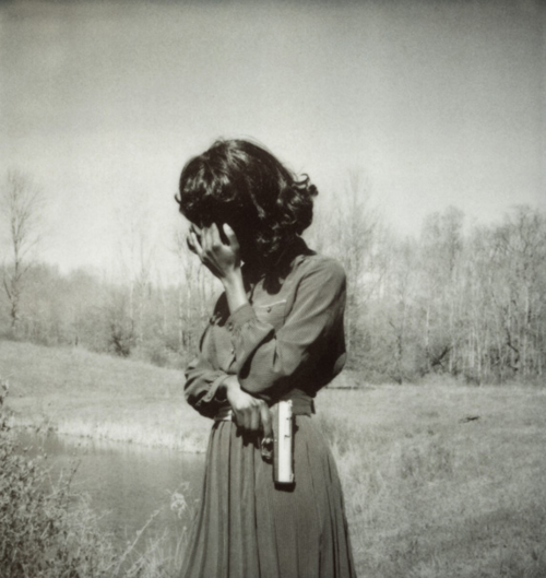 (Apparently?) old photo of a woman holding a gun (this is ominous).