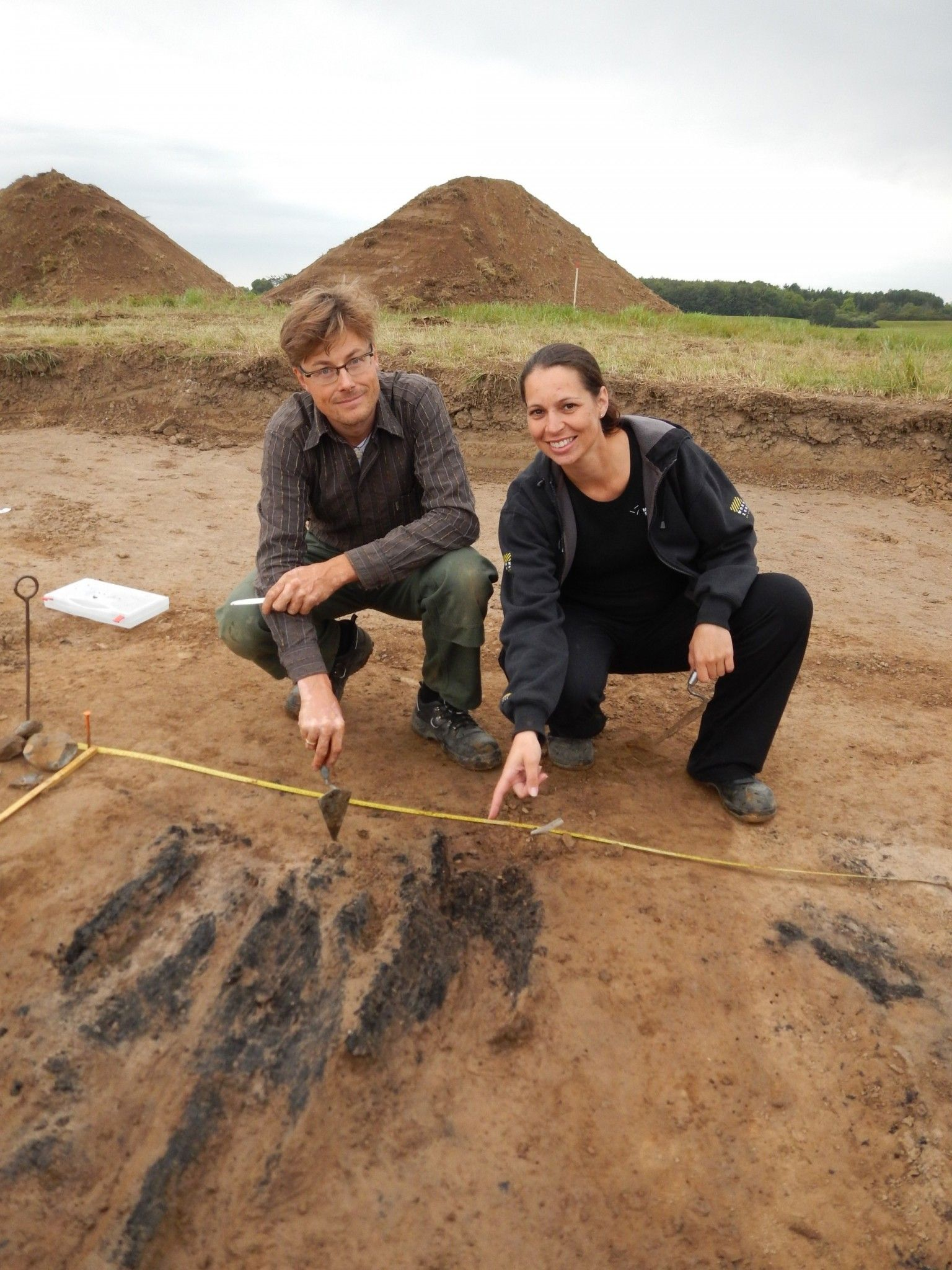 "Søren M. Sindbæk and Nanna Holm showing the remains of the charred planks at one of the gateways to the fortress. © The Danish Castle Centre. Photo from ""Has one of Harald Bluetooth's fortresses come to light?"" http://openscienceworld.com/has-one-of-harald-bluetooths-fortresses-come-to-light/ #viking #fortress #bluetooth #Harald #archaeology #history"