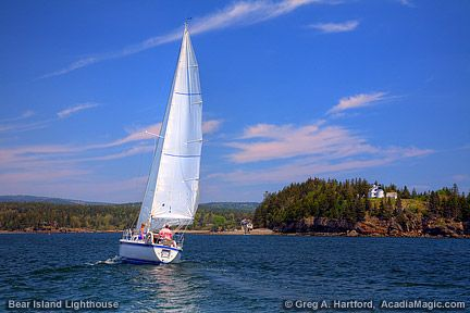One of our sailboats sails by the Bear Island Lighthouse in Somes Sound, Maine.