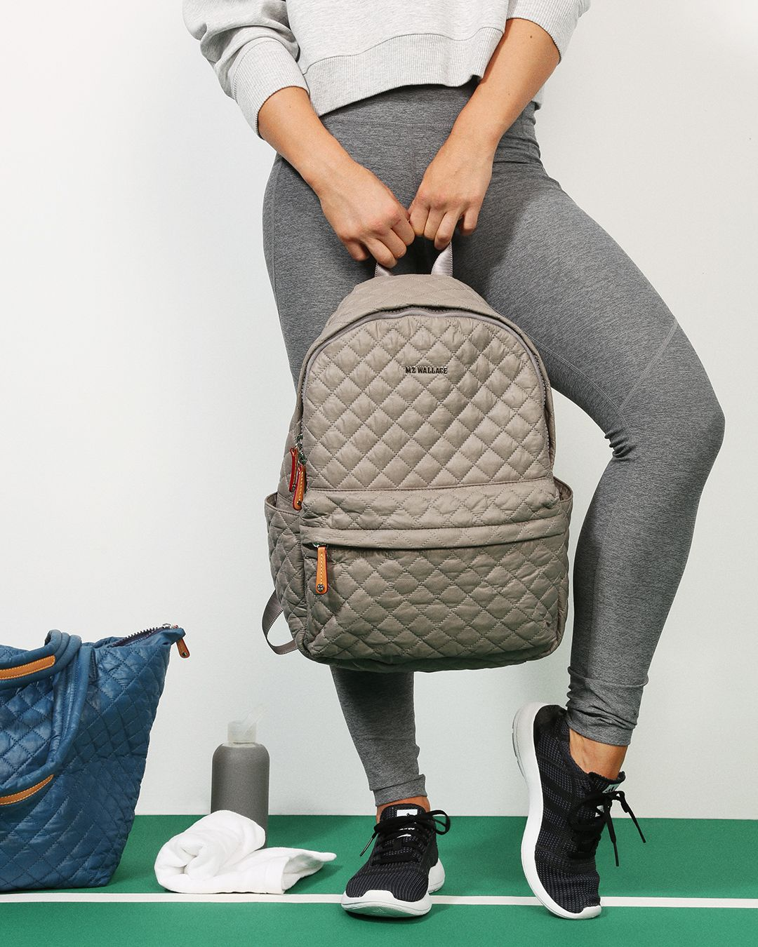 MZ Wallace Taupe Oxford Nylon Metro Backpack and Pacific Oxford Metro Tote  on the tennis court. 90984bdbc34de