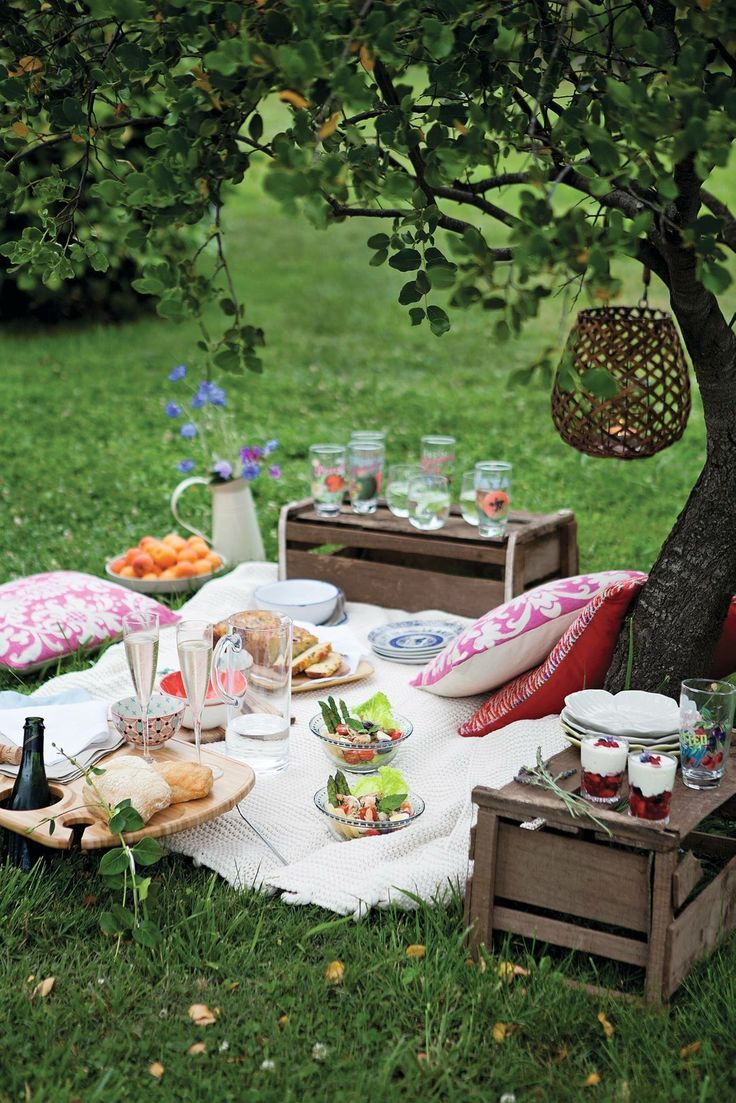 Beautiful picnic spread with wood storage crate tables,vhll hanging lantern in tree, and pillows for seating. #beauty